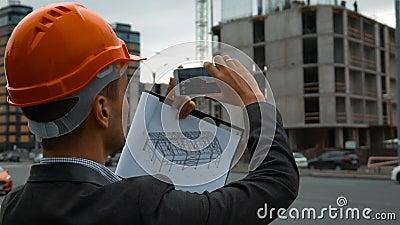 Ingenieur met de slimme telefoon die beelden van bouw nemen stock videobeelden
