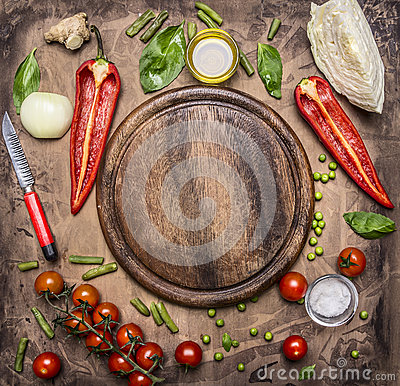 Ingredients for cooking vegetarian food bell peppers, knife for vegetables, cherry tomatoes branch and seasoning herbs place Stock Photo