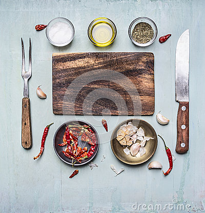 Free Ingredients For Cooking Cutting Board, Fork And Knife For Meat, Hot Red Pepper Bowl Of Garlic Butter And Seasonings Rust Stock Images - 61547604