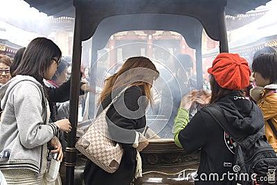 Inhaling incense smoke in Tokyo Editorial Stock Image