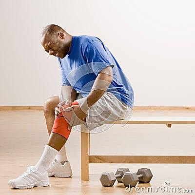 Injured man holding knee splint