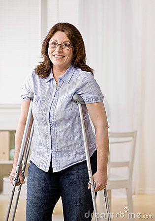 Injured woman using crutches to walk
