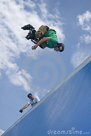 Inline skater jumping from half-pipe. Editorial Photography