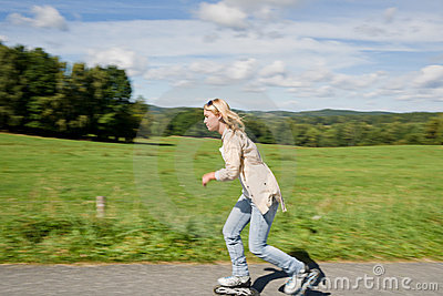 Inline skating young woman speed workout sunny day