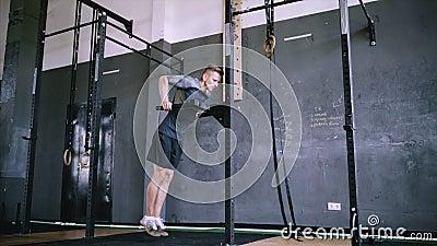 Inmersión masculina joven del tríceps que hace en un gimnasio almacen de video