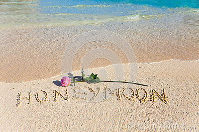 Inscription Honeymoon and rose on sea coast