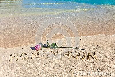 Inscription Honeymoon and rose on sea coast