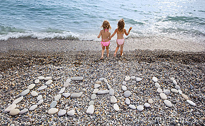 Inscription from stones BEACH at coast, two girls