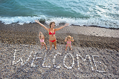Inscription from stones WELCOME at coast, family