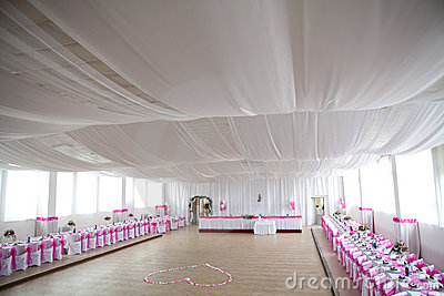 The inside of a massive white wedding tent with ta