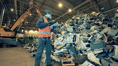 Inspetor de lixo com um tablet observando uma pilha de resíduos Fábrica eletrônica de reciclagem de lixo vídeos de arquivo