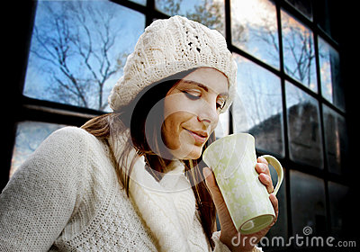 Inspired woman with mug against glass wall
