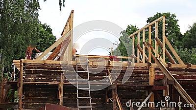 Installation d'un nouveau toit en bois sur une maison de demeure par une équipe de menuisiers et de roofers banque de vidéos