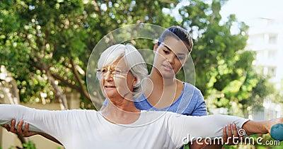 Instructor femenino que ayuda a la mujer mayor en el ejercicio con las pesas de gimnasia 4k almacen de video