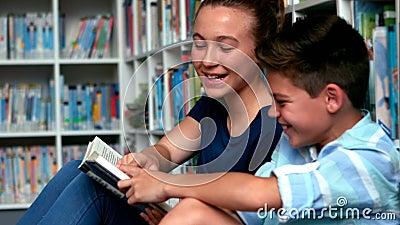 Instruisez les livres de lecture d'enfants dans la bibliothèque à l'école banque de vidéos