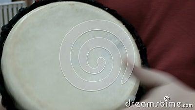 Instrumento musical de percusión, que se toca con las manos Cierre de la mano de un baterista Música étnica en un edificio modern almacen de video