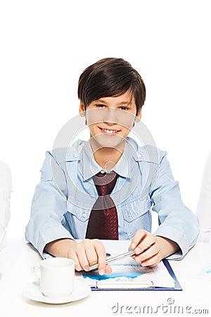 Intelligenter glücklicher Junge, der vortäuscht, ein Geschäftsmann zu sein