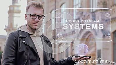 Intelligenter junger Mann mit Gläsern zeigt einem Begriffshologramm Cyber-körperliche Systeme stock video footage