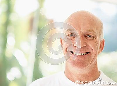 Intelligenter älterer Mann, der über einem hellen Hintergrund lächelt