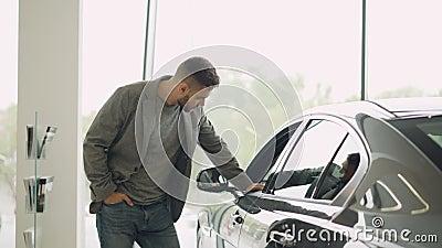 Interessierter Kunde kontrolliert schönes Automobil im Bewegungsausstellungsraum, betrachtet Auto und berührt es Fokus auf glänze stock footage