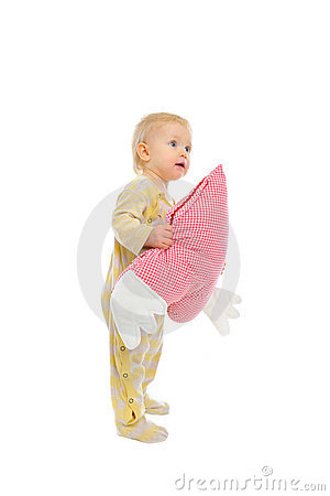 Interested baby standing with heart shaped pillow