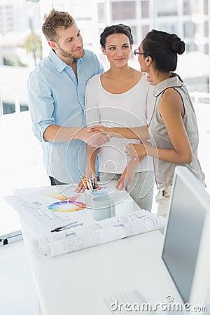 Interior designer shaking hands with happy client stock - Clients looking for interior designers ...