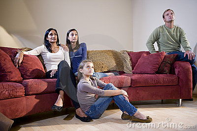 Interracial family sitting on sofa watching TV