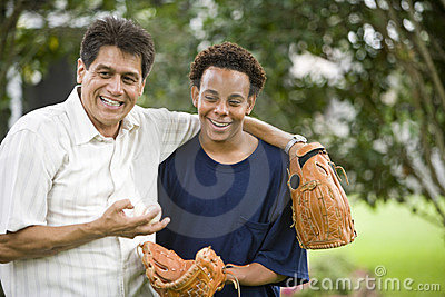 Interracial father and son with baseball gloves