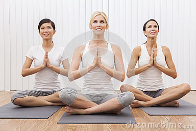 interracial group of women in yoga position stock