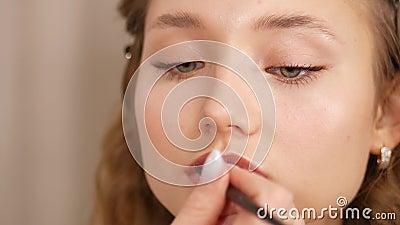 Inventare la faccia di una ragazza Applicazione di vernice alle labbra della ragazza archivi video