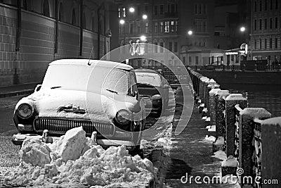 Invierno en St Petersburg: coches bajo la nieve, noche