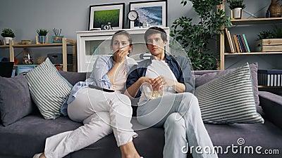Inzoomen van jonge familie die op droevige film op TV letten die popcorn thuis eten stock video