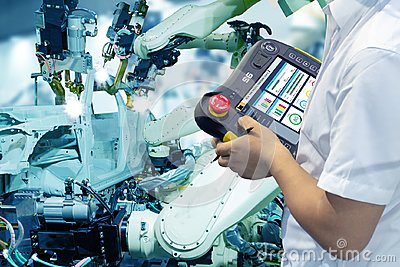 Iot smart factory , industry 4.0 technology concept, Engineer use controller robot in automation factory background with fake sunl Stock Photo
