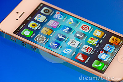 IPhone 5 Apps screen on a blue lighted surface Editorial Photography