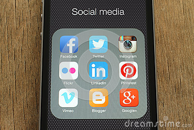 IPhone with popular social media icons on its screen on wooden background Editorial Stock Photo