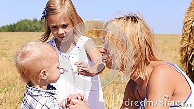 A irmã e a mamã ensinam um rapaz pequeno fundir bolhas filme