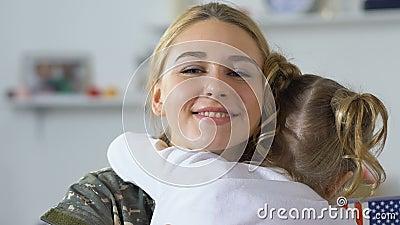 Irmã mais nova que abraça o uniforme militar da jovem mulher, celebração do Dia da Independência vídeos de arquivo