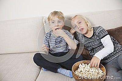 Irmão e irmã que olham a tevê e que comem a pipoca