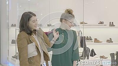 Irmãs adolescentes que olham um par de sapatas na loja da janela na alameda que discute e que ri sobre seu projeto estranho - filme