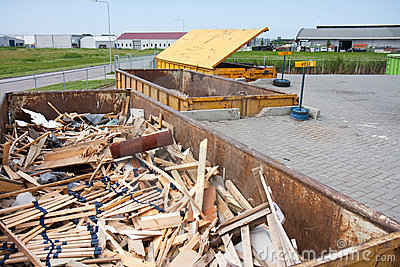 Iron dumpster with groundwood  at a refuse dump