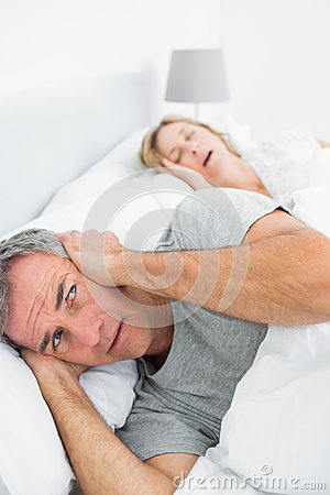 Irritated man blocking his ears from noise of wife snoring