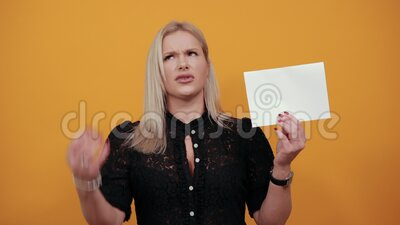 Irritated woman shows clean white sheet of paper and is nervous shows protest. Beautiful blonde girl in black dress on yellow background an irritated woman shows stock footage