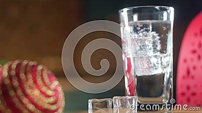 Iskkuber av kylglas som flyter i glas med mousserande vatten lager videofilmer