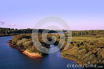 Island part on river under azure sky