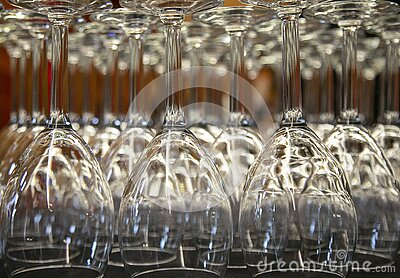 Isolated, close up view of lined up upside down commercial wine glasses Stock Photo