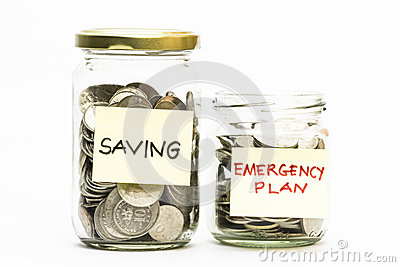 Isolated coins in jar with emergency plan and saving label.