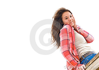 Isolated teen girl sitting on a wooden rail.