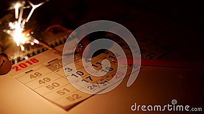 Ist auf dem Tisch ein Kalender mit Feiertag datiert die Feiertage des neuen Jahres, Wunderkerzen brennen und ein Bleistift liegt, stock footage