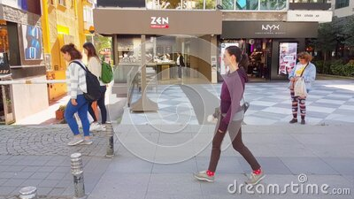 Caucasian woman walking alone near cafes and shops in Bagdat Street at the weekend. Istanbul, Turkey - October 05, 2018: Side view of a young Caucasian brunette stock video