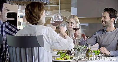 Italiaanse mensen die toost samen met rode wijn maken Vier gelukkige echte spontane vrienden genieten samen van hebbend lunch of  stock video